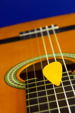 Closeup detail of a classic guitar and yellow plectrum over blue background photo