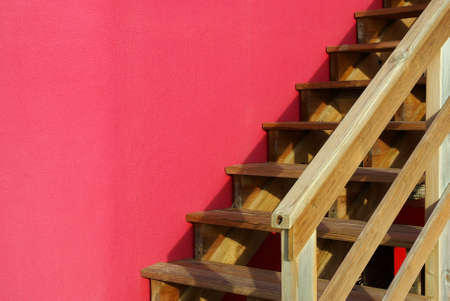 Detail of an outdoor wooden stairway against a pink wall photo