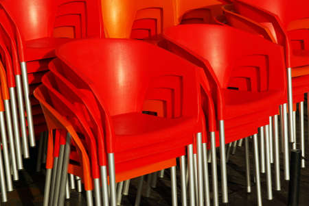 Close-up on a pile of red plastic chairs shining under the sunlight  photo