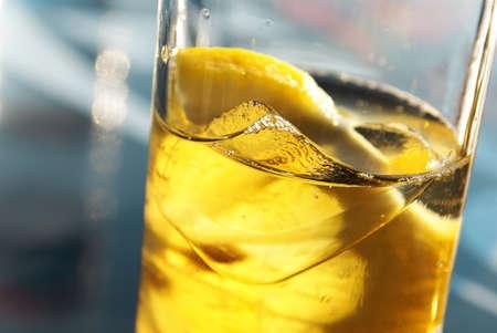 Primer plano de un vaso con la bebida, sector de limón y hielo y luz solar desde detrás  Foto de archivo - 8807423