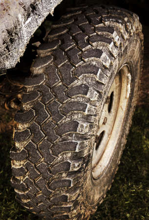 fourwheeldrive: Detail of a muddy off-road vehicle tire over dirty grass Stock Photo