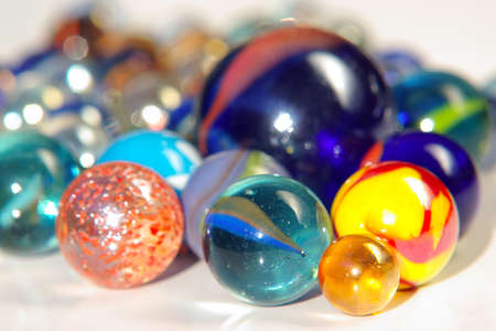 Handful of colorful glass marbles over white background.  photo