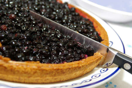 blueberry pie: Closeup of a beautiful blueberry pie with a knife cutting a slice