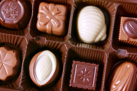 boxed: Closeup on a box of assorted tasty brown and white chocolates Stock Photo