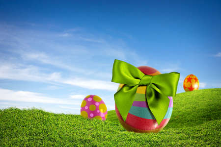 Three colorful Easter eggs with green bow on a grass field