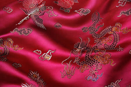Closeup of a red silky chinese fabric with oriental motifs