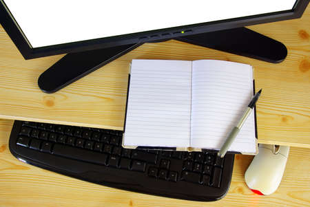 Computer desk with monitor, keyboard, mouse and an opened notebook and pen Stock Photo - 9082804