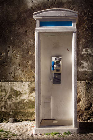 Old white and blue phonebooth in an old city street photo