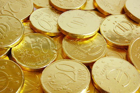 coin stack: Pile of chocolate coins wrapped in shiny golden tinfoil Stock Photo