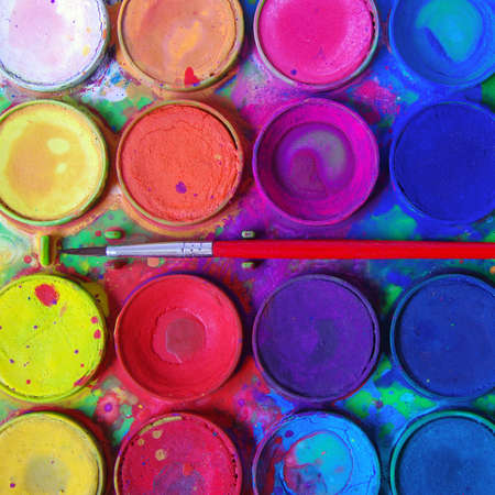 pigments: Closeup of messy, used water-color paint-box and paint brush.
