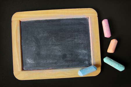 Dirty and used old slate and pieces of colored chalk
