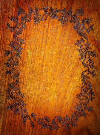 Old wooden background with frame of carved floral motifs photo
