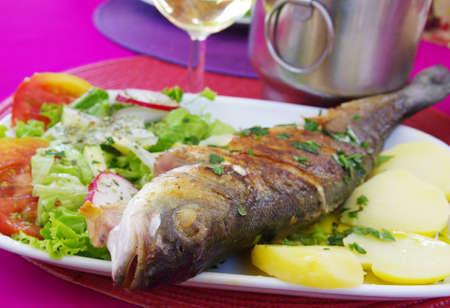 Gegrillter Wolfsbarsch mit Kartoffeln und Salat serviert in einem rosa Tisch Standard-Bild