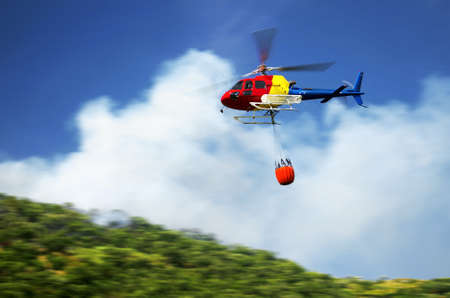 Firefighter helicopter in action flying over a fire in the mountains photo