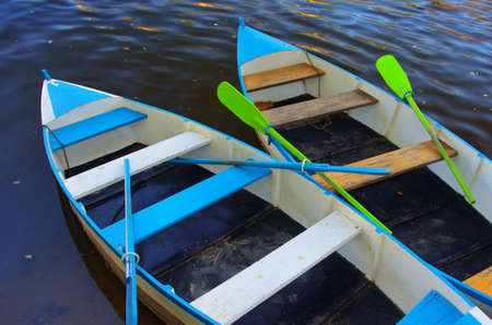 Two blue row boats anchored in a river shore photo