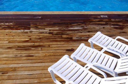 pool deck: Top view of two empty white deck chairs in a swimming pool Stock Photo