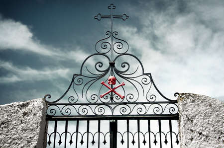 iron cross: Detail of an ancient cemetery gate with a skull and crossed bones painted red