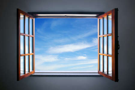 Wide open rustic window showing a blue sky outside photo