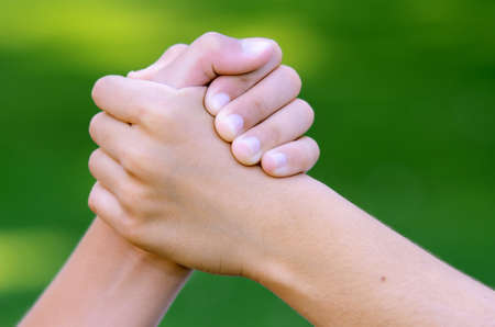 Cool handshake between two friends against green background