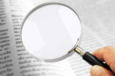 Hand houden van een vergrootglas lens over wazig pagina's van een open boek Stockfoto