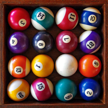 Top view of a full set of snooker balls inside an old wooden box
