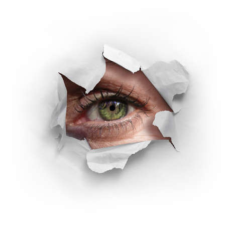 Female green eye looking through a ripped hole in a white paper Standard-Bild