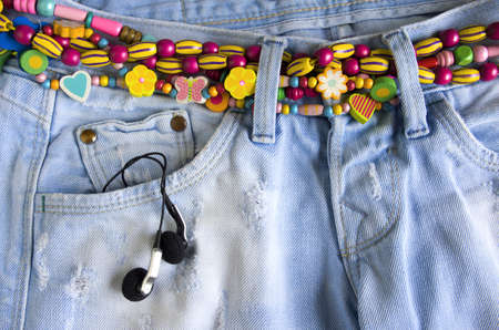 Close-up of worn blue jeans with headphones in the pocket and colorful belt of beads photo