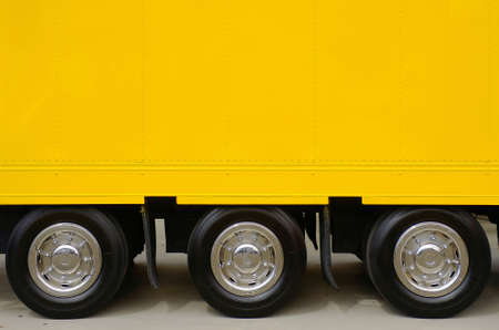 big wheel: Detail of the empty yellow side of a large truck with three wheels Stock Photo