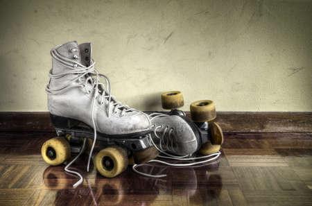 patinar: Vintage patines de rodillos de grandes cordones de los zapatos en una pared de fondo amarillo