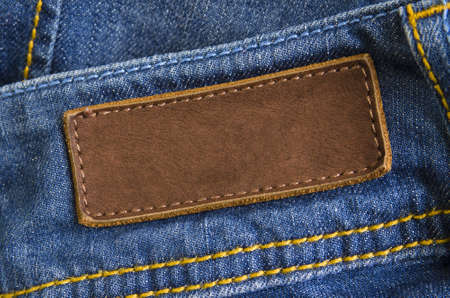 Close-up of old leather tag with copy space, sewed on blue jeans back