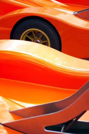 autos: Details of two orange racing car body design showing spoilers a a wheel