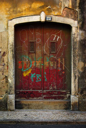 Damaged res wooden door of an old urban house photo