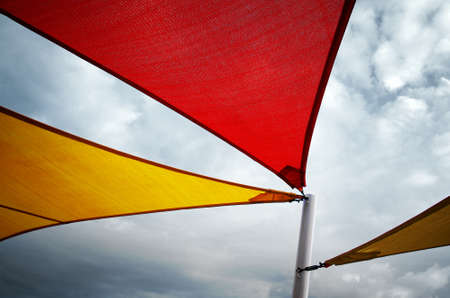 angular: Three angular canvas awnings supported by a white pole against a cloudy sky Stock Photo