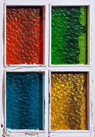 Old window with white frame and colorful glass resembling a known software logo