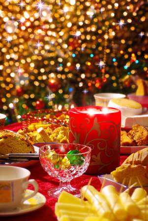 decoracion de pasteles: Tradicional mesa de Navidad con el conjunto de tazas de té, pasteles, queso y una vela y las luces brillantes en el fondo.