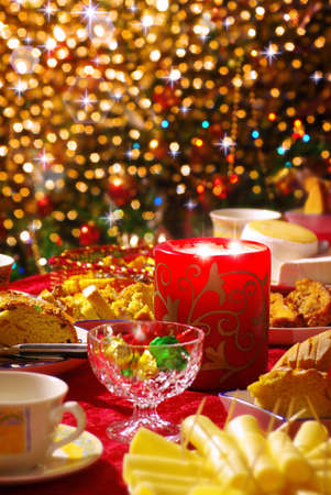 Traditional Christmas table set with tea cups, cakes, cheese and a candle and sparkling lights in the background.