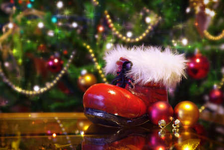 santaclaus: Christmas tree and decorations and a santa-claus boot on a table