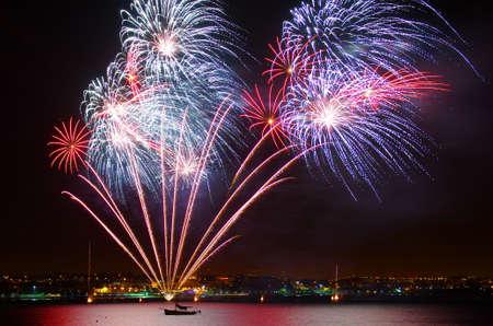 tűzijáték: Új év ünnepe színes tűzijáték alatt a tenger közelében, a tengerparton