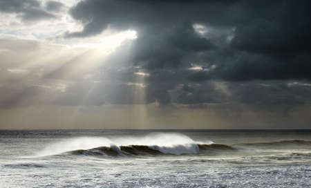 Beautiful seascape with bright sun rays and dark clouds over a wavy sea photo