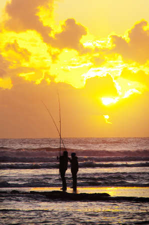 Silhouette of two fisherman fishing in the sea shore at sunset photo