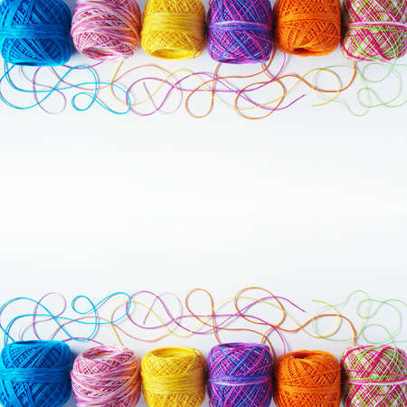 Colorful knitting yarn coils over white background