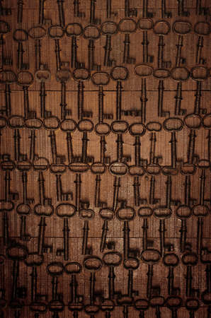 Background image of rows of rusty old keys nailed to a brown wooden wall photo