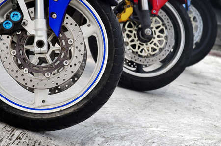 Row of three motorcycle wheels parked in a road photo