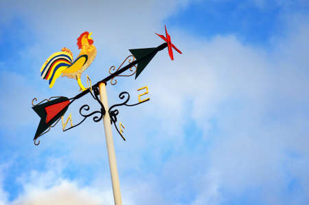 Colorful weather vane with cock figure over cloudy sky