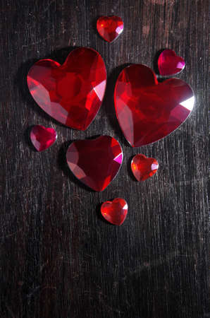 valueables: Several heart shaped red rubi gem stones over a scratched wooden background Stock Photo