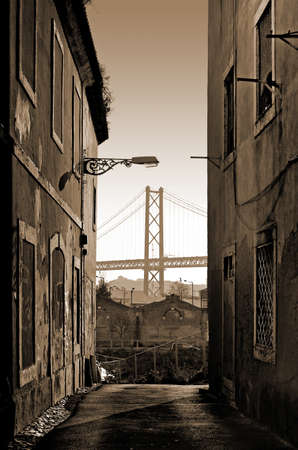 Narrow old street with abandoned buildings and view to the bridge 25 April in Lisbon, Portugal