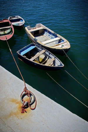 Four fishing row boats anchored in a dock with a red rope tied in a iron ring