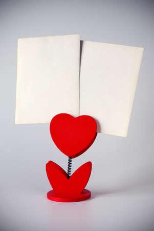 heart-shaped photo holder holding two blank photos photo