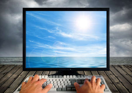 Conceptual image of a computer monitor and keyboard being operated outdoors by the seashore Stock Photo - 11936221