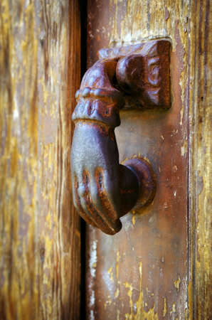 Close up on a rusty iron door knocker in a decaped old wooden door Stock Photo - 12421667